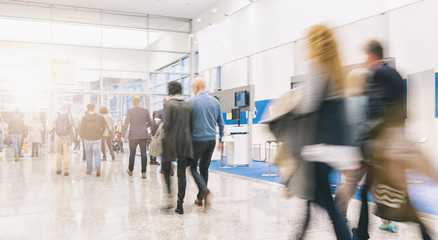 blurred people rushing at a trade fair hall