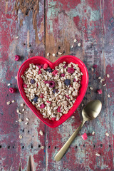 Red heart bowl filled with granola with dried red and blue berries on red rustic table top view