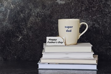 Father's day composition. Books with cup of tea on top. Father's day concept