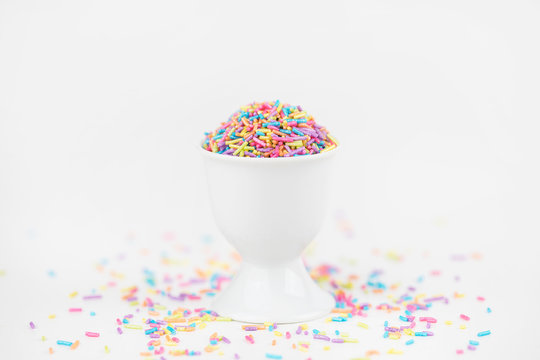 Colorful Pastel Sprinkles in a cup on white backdrop with copy space
