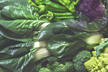 Ingredients of healthy green food. Background with Swiss chard, broccoli, peppers, Romanesco, violet cauliflower