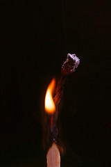 An igniting match against black background