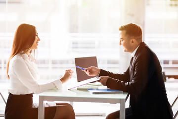 Business man and business woman sign a contract. Satisfied with loan terms woman singing contract while sitting at desk in front of male bank employee at office.