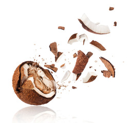 Broken coconut with splashes of juice close-up, isolated on white background