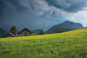 Grassy field with old wooden barn against mountain under thundercloud