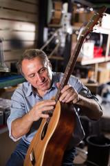 Man is repairing acoustic guitar