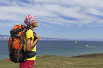 young tourist girl with a backpack on the mountain lake Baikal, summer walk, hiking, Siberia