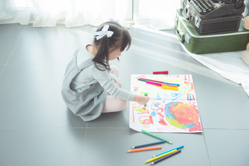 Little asian girl sitting on the floor and drawing picture by crayon and pencils