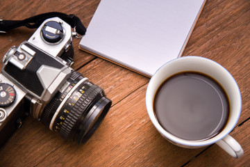 Coffee cup top view and camera and notebook on wooden vintage table background