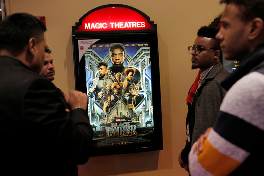 """A group of men gather in front of a poster advertising the film """"Black Panther"""" on its opening night of screenings at the AMC Magic Johnson Harlem 9 cinemas in Manhattan"""