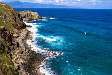 Volcanic rock, surf, and shades of the blue Pacific Ocean on the Maui coast, with the island of Molokai in the background