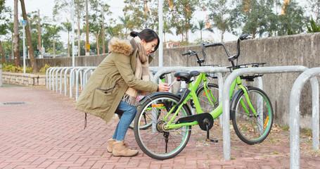 Woman using share bike in city