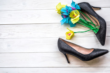 spring paper flowers in a lady shoe on white wooden background. flower gift on a women's day. black shiny high heels on white wooden background