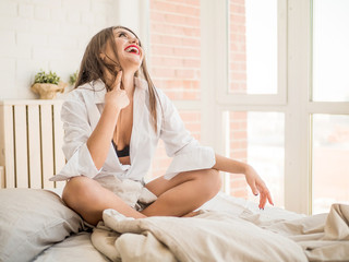Young woman laughing at a something funny as she relaxes in bed with her laptop computer looking to the side