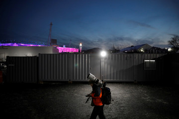 A photographer walks as the Olympic cauldron is seen in the background in Pyeongchang