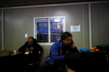 The Olympic cauldron is seen through a window of a venue media centre as journalists work on the Medals Plaza in Pyeongchang