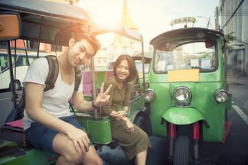 young traveling man and woman sitting on tuk tuk domestic vehicle in yaowarat road heart of bangkok thailandd