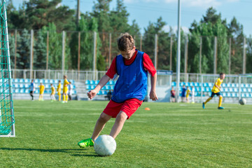 boy trains dribbling on the summer stadium during the training
