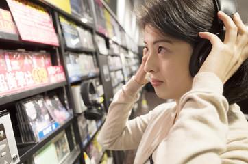 CDを視聴視聴しながらタイトルを確認する女性