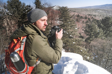 Landscape photography: a man hiker with a backpack shoots a landscape in a winter forest
