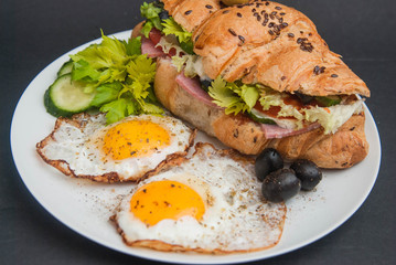 Breakfast with Fried Eggs and Sandwich Croissant on White Plate on black Background.