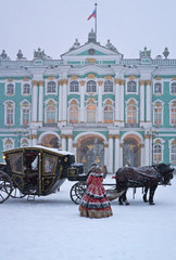 St. Petersburg in the winter. The Winter Palace, an old carriage and a woman in traditional Russian clothes on the Palace Square during a heavy snowfall