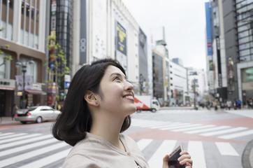 女性が都心の交差点で空を見上げている。