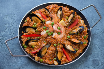 Frying pan with spanish traditional paella over blue stone background, studio shot, selective focus