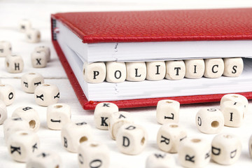 Word Politics written in wooden blocks in red notebook on white wooden table.