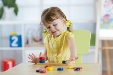 Smart child girl plays in kindergarten in Montessori preschool class.