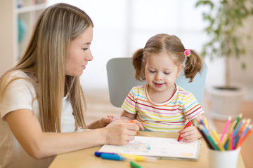 Little child girl coloring with felt pen next to her mother in nursery room.