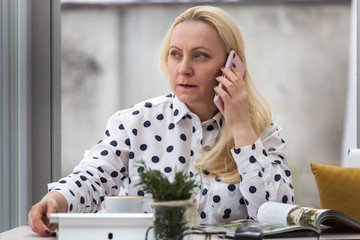 Beautiful adult woman with blond hair works in a cafe with a white interior. The company management by talking on the phone.