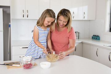 blond woman cooking and baking happy together with sweet adorable mini chef little girl at home kitchen in mother and daughter love