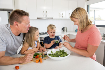 young attractive couple mother and father preparing salad together with little son and young beautiful daughter in healthy vegetable nutrition