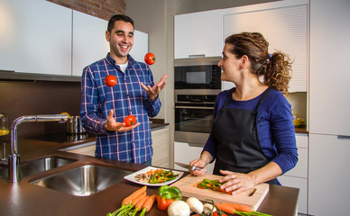 Woman cutting vegetables to prepare food while her husband juggles tomatoes