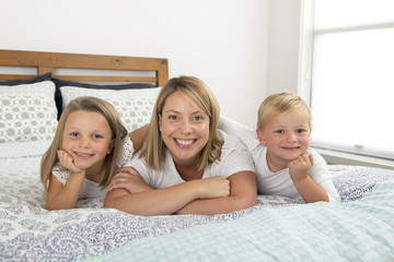 young blond Caucasian woman lying on bed together with her little sweet 3 and 7 years old son and daughter smiling playful and happy