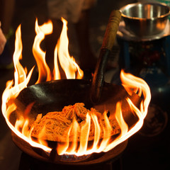 Chef cooking with fire with frying pan. Chef frying food in flaming pan on gas hob.
