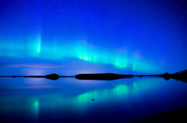 Northern lights dancing over calm lake. Farnebofjarden national park in Sweden