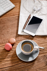 stylish still life with an espresso coffee macaroons and french pastries on a rustic wooden tables with smartphone earphone and newspaper