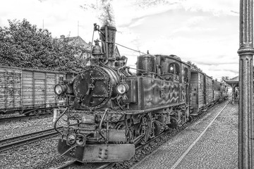 Historic steam powered railway train at train station in black and white