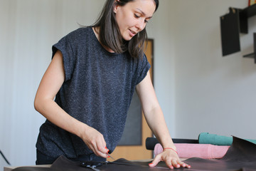 seamstress got high-quality material for bags from friend living abroad. Smiling girl with kare haircut and red nails unwrapping roll of leather on table in workshop at home. Concept of expen