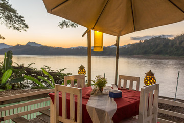 Empty table in cozy cafe overlooking the Mekong river in Luang Prabang, Laos