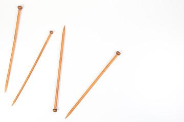Wooden knitting needles on white background as frame