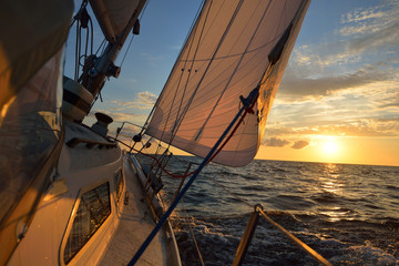 View from the deck of a strongly tilted yacht on a windy day in an open sea on sunset