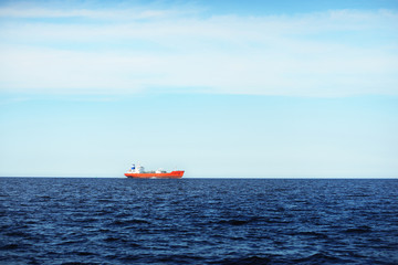View of a distant red lpg tanker sailing in a open sea on a clear day