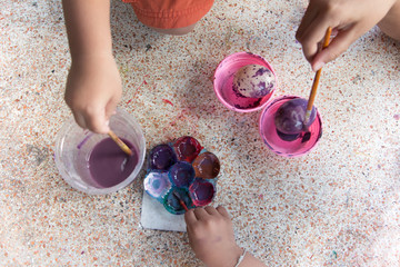 The children are painting The Easter eggs for funny.