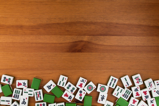 White-green tiles for mahjong on a brown wooden background. Empty space above