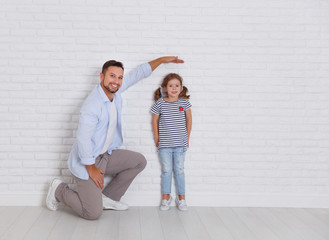 concept of the family. the father measures growth of child to daughter near empty wall