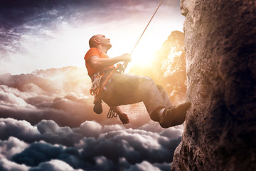 Man wearing shirt using rope to climb steep cliff