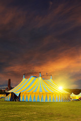 Circus tent under a warn sunset and chaotic sky without the name of the circus company which is cloned out and replaced by the metallic structure
